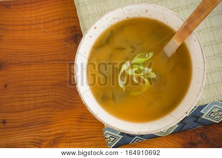 Japanese yellow awase or mixed miso soup with chopped spring onion or scallions top down view