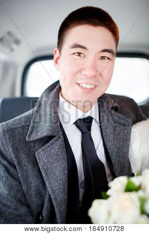 The groom in a winter coat sitting in the car with a wedding bouquet in hands. Positive portrait, looking into the camera. White shirt with a tie.