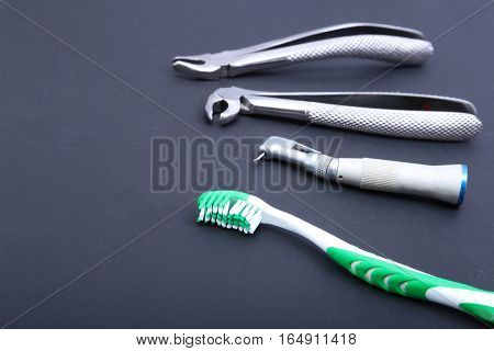 dental care toothbrush with dentist tools on black background