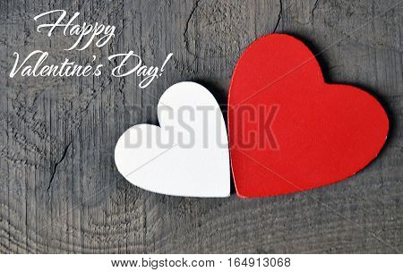 Happy Valentines Day background. Decorative red and white wooden hearts on a grey rustic wooden background.Two Valentine hearts.Saint Valentine's Day concept.Selective focus.
