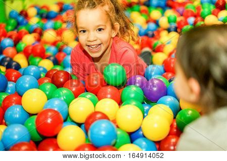 Cheerful children playing inside ball pit swimming pool - Happy people having fun in baby playground indoor - Childhood and friendship concept - Soft focus on left female face - Warm vivid filter