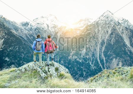 Two hiker friends at peak of the alps mountains in france looking the panorama view - People doing trekking at sunset with back light - Extreme sport and survival concept - Warm filter with sun flare