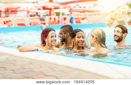 Happy friends swimming in aqua park pool for summer time vacation - Young diverse ethnic people having fun diving in water with sun back light - Friendship concept - Focus on left girls - Warm filter