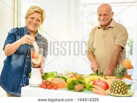 Senior couple preparing vegetarian breakfast with bio organic ingredients at home - Retired people taking care about nutrition and diet - Healthy lifestyle concept - Focus on man face - Warm filter