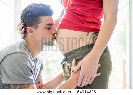 Young tattoo modern couple waiting for a male baby - Happy future dad kiss the belly of his pregnant woman with back sun light at home - Love and parenthood concept - Focus on man face - Warm filter