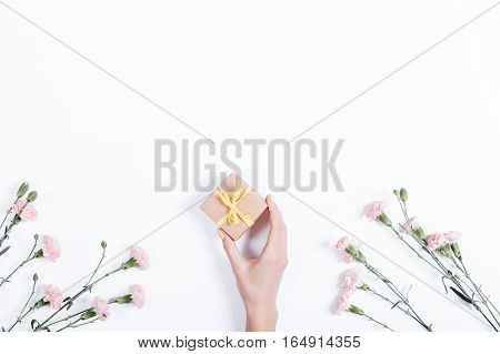 Little Pink Carnation On A White Background And A Woman's Hand With A Gift In A Small Box, Space For