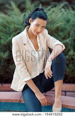 Confident woman - portrait of happy beautiful mixed race Asian Caucasian young businesswoman in casual clothes outdoor sitting in park