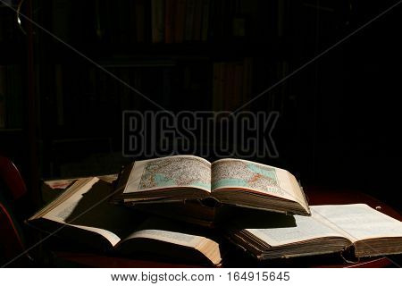 Opened Book Lying On A Black Background. Study And Reading.