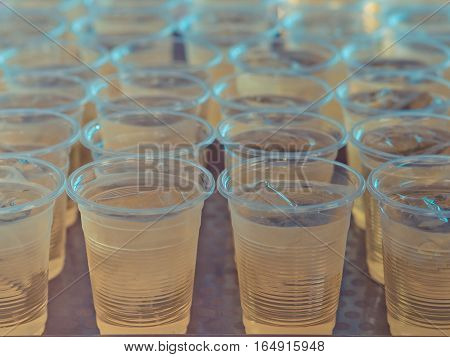 Yellow water in plastic glasses. on the table.