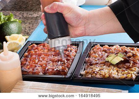 Chef Adding Sauce To Japanese Food
