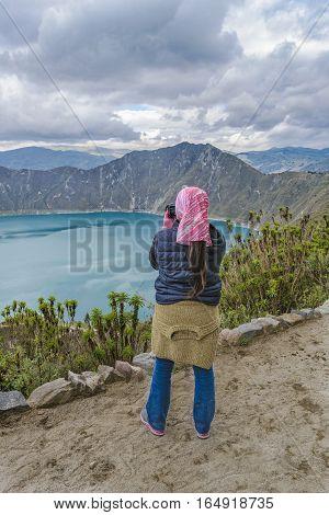 Young woman taking photo at viewpoint in Quilotoa lake Latacunga Ecuador