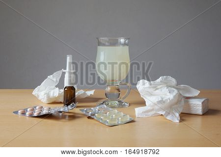 common cold or flu remedy. hot lemonade, nasal spray, pills, and tissues