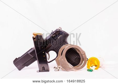 Clip, prescription bottle, drugs, gun, handcuffs and bullets with white background.