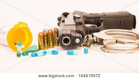 Prescription bottle, drugs, gun, handcuffs and bullets with white background.