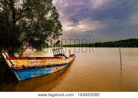 A old sunken crab boat grounded along Krabi river side on the Andaman penisula in Thailand