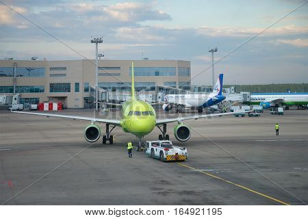 MOSCOW, RUSSIA - MAY 03, 2016: Towage of the Airbus A319 plane (VP-BTV) of S7 airline in the May evening at the Domodedovo airport