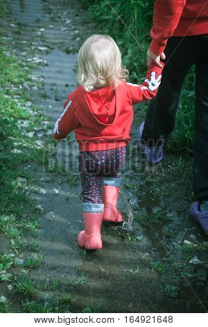 Rear view of little baby in red hood and gumboots holds her mother's hand and walking through the puddles