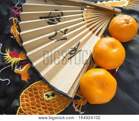 Chinese New year, tangerines and a fan lying on the silk fabric with an embroidered dragon.