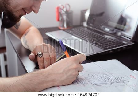 An artist with a beard encircles pen sketch drawn tattoos. Creature. Handmade.