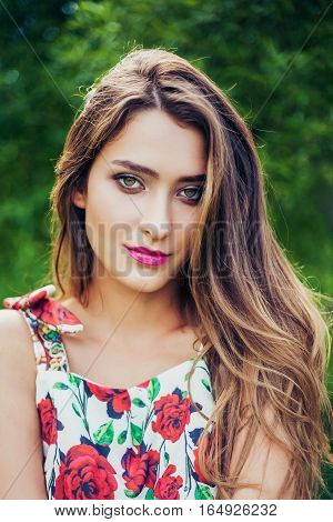 Portrait of young beautiful woman wearing trendy summer outfit posing in park. Professional make-up and hairstyle. Perfect skin. Fashion photo. Natural beauty.
