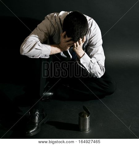 businessman lost everything and is now desperately sitting on the ground with a tin can in front of him, begging