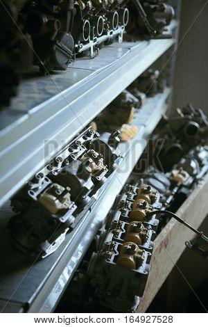 Close up of motorcycle's carburetors lying on shelf in garage