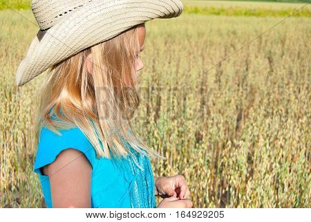 young girl wearing western style hat in wheat field