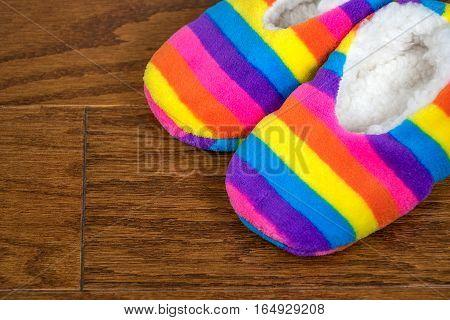 bright rainbow striped slippers on wood floor