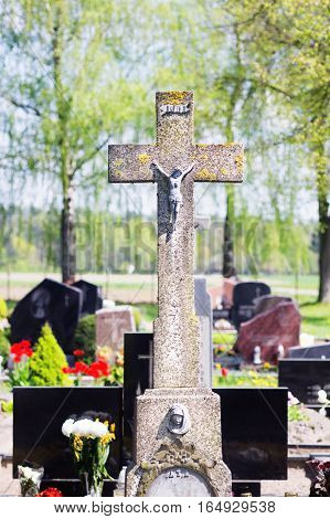 Concrete old cross with crucifix in cemetery in summer.