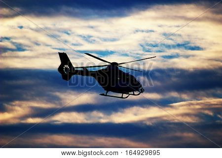 silhouette of flying rescue helicopter flying for victim of car accident with visible fumes of exhaust gases on the left side