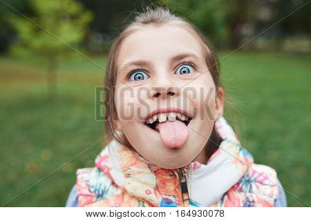 Closeup portrait of a cute little girl making and face and sticking out her tongue while playing outside in the autumn