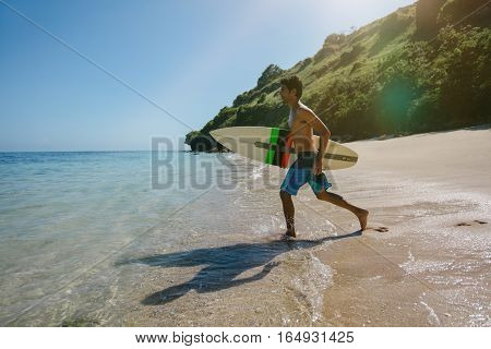 Shot of handsome young man with surfboard going for surfing in the sea. Surfer carrying his surfboard running on the beach.