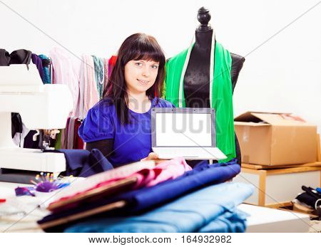 a female fashion designer is working on a new piece of clothing in her somewhat chaotic studio. in this shot, she is holding a laptop, possibly showing her online store. laptop screen is plain white so you can easily paste in your own content.