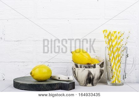Cookware in gray cups, plates, bowls, cutting boards round against a white brick wall in horizontal design with the addition of fresh, juicy lemons. Selective