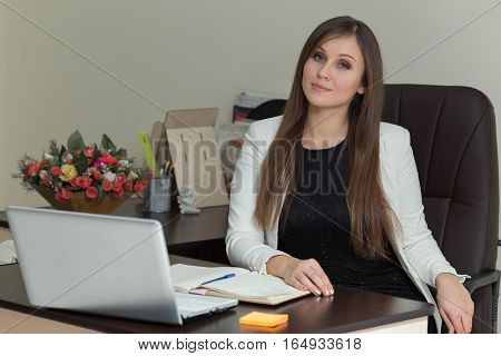 Relaxed Young Businesswoman Sitting At Her Desk.