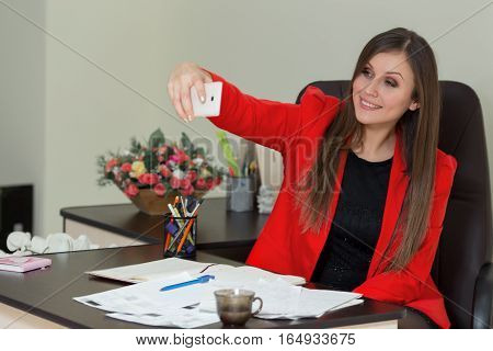 Young Business Woman Is Photographed On A Smartphone In Office.