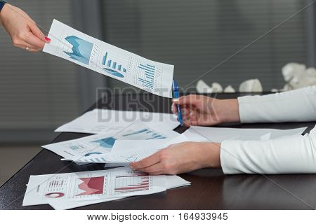 Cropped Image Of Business Woman Giving Progress Chart To Colleague At Desk In Office.