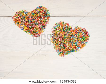 Candy sprinkles form heart shape. Multicolored heart-shape from candy confetti on white wooden background. Valentines day concept. Top view or flat lay with copyspace.
