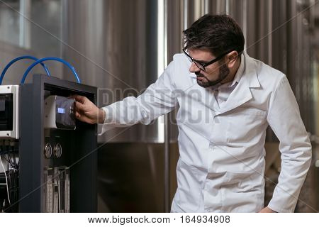 Responsible and smart. Handsome delighted young man using brewing mechanism while working in brewery and wearing glasses.