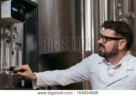 Smart and responsible. Concentrated delighted young man using brewing mechanism while working in brewery and wearing glasses.