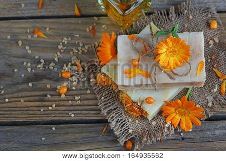 Natural handmade soap with calendula and sea-buckthorn on rustic wooden background