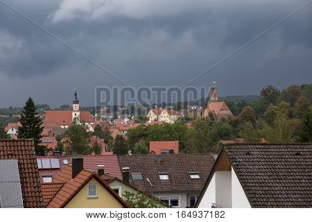 Hilpoltstein With Catholic Parish Church St. Johann Baptist And Castle Ruin Under Stormy Sky