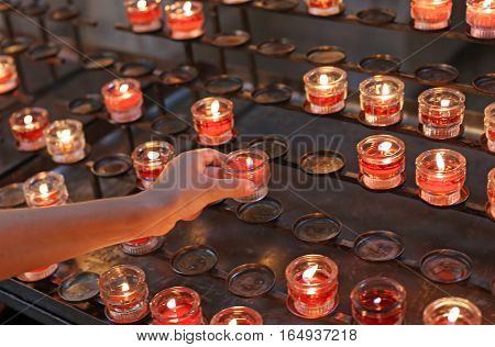 Child Lights A Red Candle In Church And Then Say A Prayer For Th