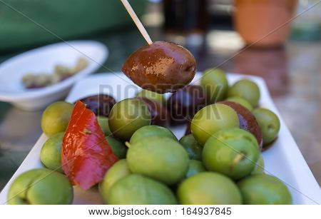 Black Olive caught with a toothpick from a spiced olives plate on tapas bar table a typical Spanish black and green split variety