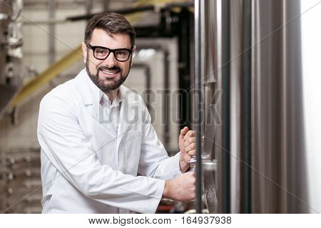Do it good enough. Overjoyed young delighted man working on beer factory while using mechanism and wearing glasses.