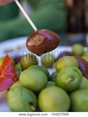 Extreme Close-up of Black Olive caught with a toothpick from a spiced olives plate on tapas bar table a typical Spanish black and green split variety in detail. Vertical view