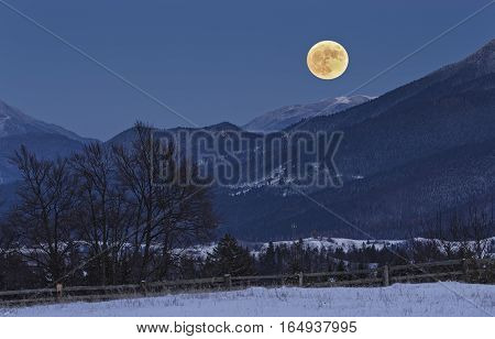 Enchanting nocturnal rural scene with full moon rising over the Piatra Mare (Big Rock) peak as seen from Fundata village in Rucar-Bran pass Romania.