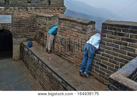 The Great Wall of China in early spring; one of a series of pictures. This image has been enhanced with a HRD filter to make the details and colors pop. The image shows two women leaning out over a parapet looking down below.