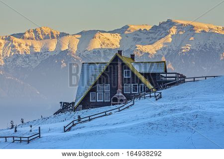 Alpine scenery with rustic wooden cottage and yellow snowcapped ridge of the Bucegi mountains in the sunrise light on a cold serene winter morning in the Bran-Rucar pass Transylvania Romania.