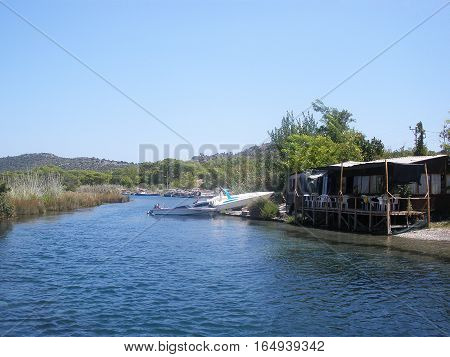 Kekova Turkey - August 14 2012: Kekova. lonely cafe by the river. boats. the mountains in the background